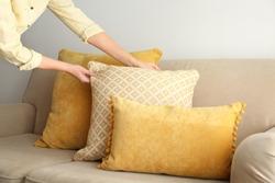 Woman arranging pillows on sofa, closeup view. Interior design