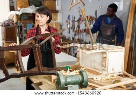 Woman artisan inspecting old chair before renovation in woodwork studio