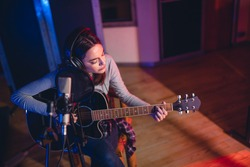 Woman artist playing guitar in a recording studio. Female singer performing a song in studio.