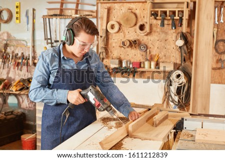 Woman as a carpenter apprentice works with a drill in the workshop