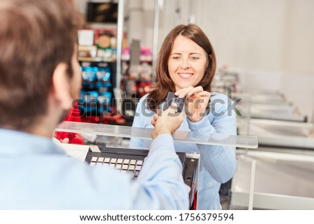 Woman as a customer at the supermarket cashier pays by credit card or loyalty card Photo stock ©