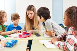 Woman as a teacher helps with homework or gives tutoring in elementary school