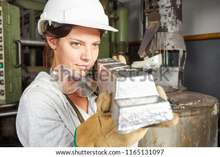 Woman as metallurgy worker holding steel workpiece and making quality control