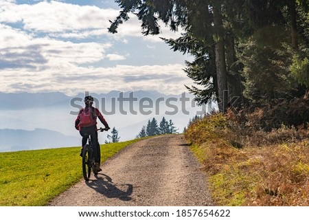 Woman as silhouette riding her electric mountain bike in the Allgaeu alps near Oberstaufen with awesome view into the Bregenz Wald Mountains, Vorarlberg Switzerland Stock foto ©