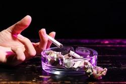 Woman ashing cigarette on dark background, closeup