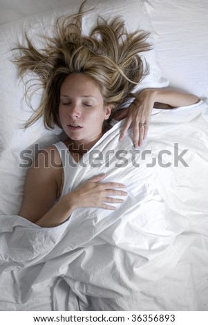 Woman asleep in bed wrapped in white sheets