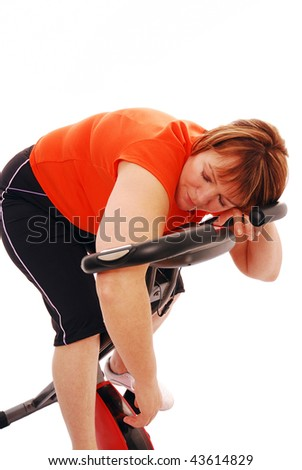 Woman asleep on exercise bike over white