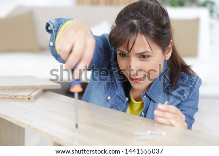 woman assembling furniture at home
