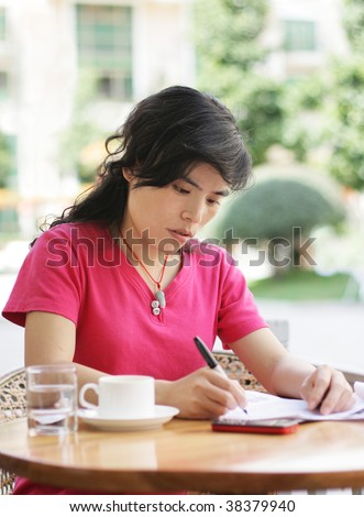 woman at a cafe writing on a sheet of paper - stock photo