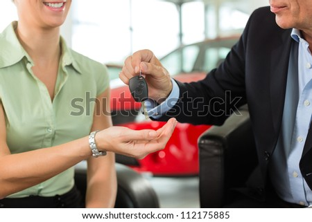 Woman at a car dealership buying an auto, the sales rep giving her the key, macro shot with focus on hands and key