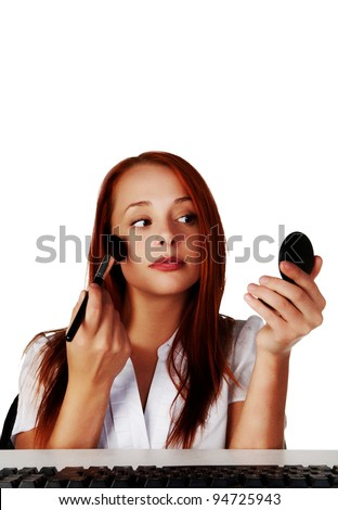 woman at a desk touching up her make up