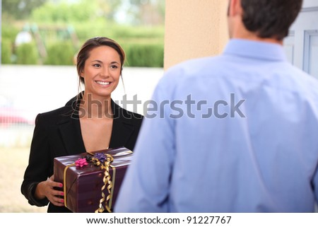 Woman at a front door with a gift