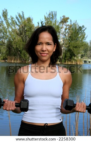 Woman at a park doing bicep curls with weights shot from waist up