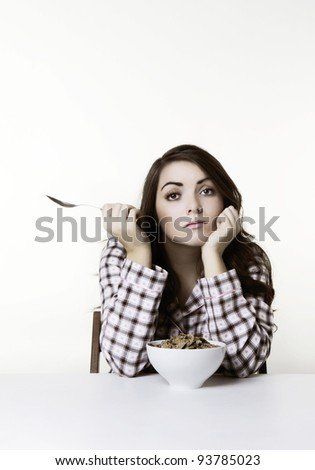 woman at a table in pajamas about to eat cereal. Please note this image has had a half colour and black and white with a sepia toning effect added.