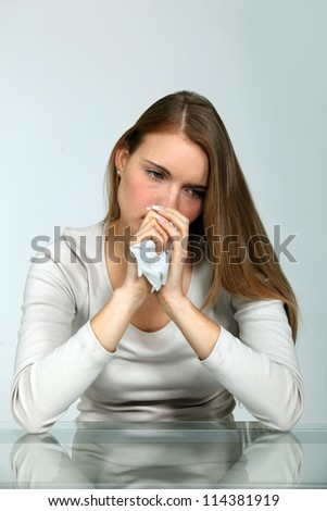 Woman at a table with a tissue - stock photo