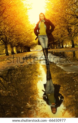 Woman at autumn outdoors walking on puddle - stock photo