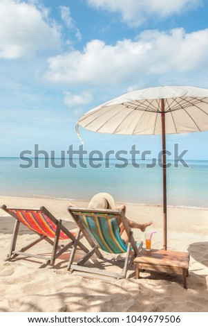 Woman at beautiful beach sitting on chaise-lounge and drinking cocktail top view #1049679506