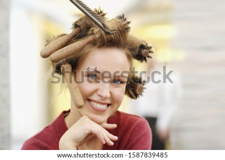 Woman at beauty salon with brushes in her hair