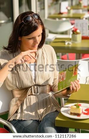 Woman at cafe bar terrace choosing from menu sunny day