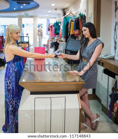 Woman at cash register paying with credit card in clothing store