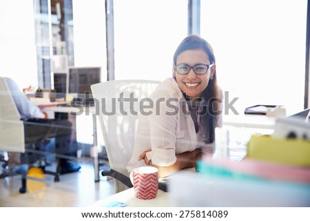 Woman at her desk in an office smiling to camera #275814089
