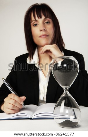 woman at her desk with a large egg timer and the grains of sands are running out