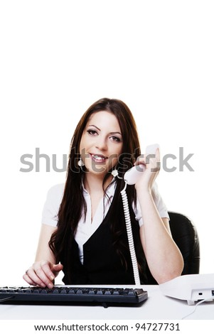 woman at her desk working and taking a call on the phone