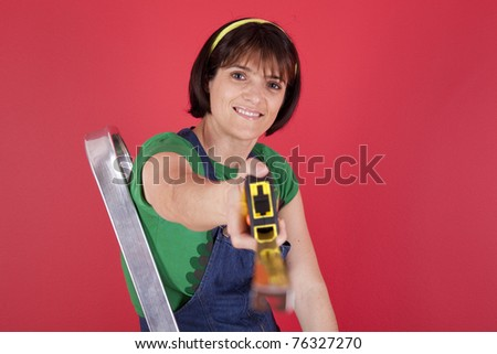 Woman at her house with a measure tape - stock photo