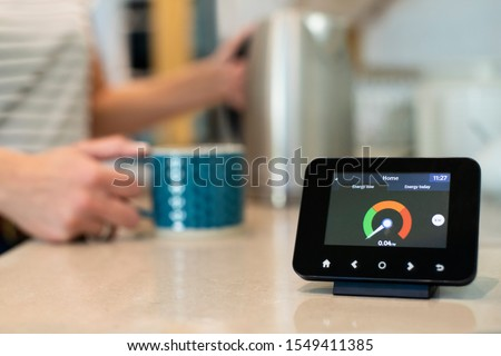 Woman At Home Boiling Kettle For Hot Drink With Smart Energy Meter In Foreground Photo stock ©