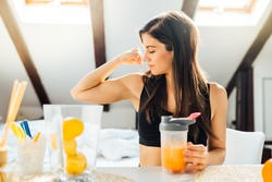 Woman at home drinking orange flavored amino acid vitamin powder.Keto supplement.After exercise liquid meal.Weight loss fitness nutrition diet.Immune system support.Organic citrus fruit drink