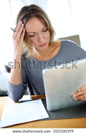 Woman at home having trouble to fill in tax form