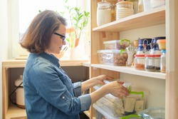 Woman at home in kitchen, near wooden shelves with food, household utensils, jars and containers with food supplies