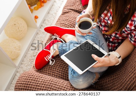 Woman at home relaxing on sofa couch reading email on the tablet computer wifi connection #278640137