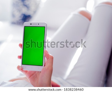 Photo of  Woman at home relaxing reading on the smartphone with pre-keyed green screen