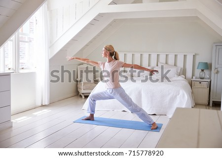 Woman At Home Starting Morning With Yoga Exercises In Bedroom #715778920