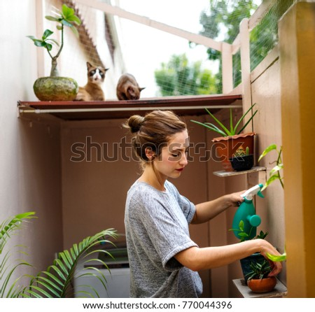 Woman at home with plants and cats
