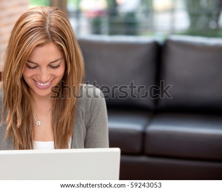 Woman at home working on a laptop computer and smiling