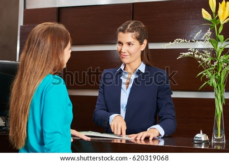 Woman at hotel reception offering advice with city map #620319068