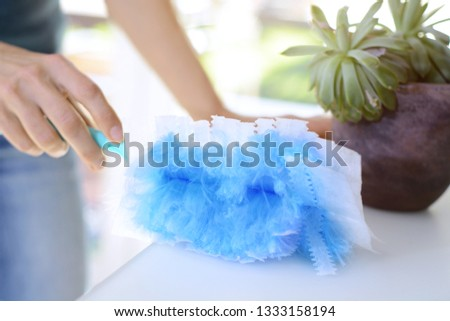 Woman at housework wipes dust with a duster #1333158194