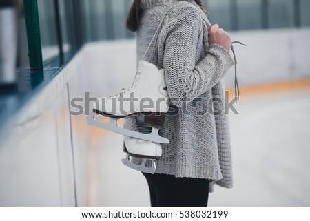 Woman at ice-skating rink holding skates. #538032199