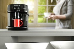 woman at morning time and black coffee machine