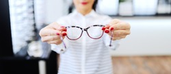 Woman at optician holding eyeglasses she want to buy. Selective focus on glasses.