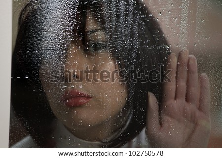 Woman at rainy window in dark rough weather