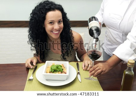 woman at restaurant, chef pouring wine into wineglass