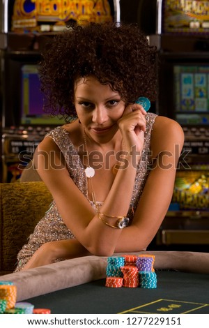 Woman at roulette table in casino holding gambling chip at camera