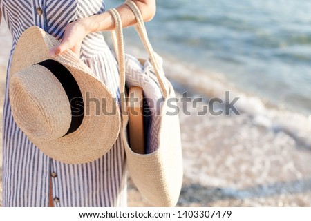 Woman at sea beach. Girl holds straw hat and bag with book and plaid. Traveler is enjoying summer vacation and holidays. #1403307479