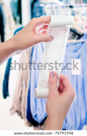 woman at shop holds in her hands roll of paper with printed receipt