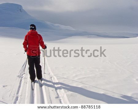 Woman at ski resting standing in a groomed single ski track with a mountain summit enjoying the gradual lighting conditions in the background in the norwegian mountains at easter