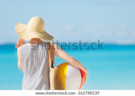 woman at the beach back view holding beach ball and bag #262788239