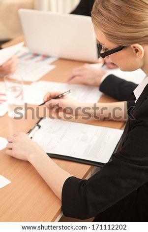 Woman at the business meeting. Top view of woman in formalwear writing something in her note pad while sitting at the business meeting